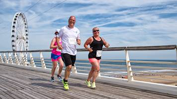 A man and woman running jogging along Scheveningen pier, during the 5k event at the Aramco Beach Run