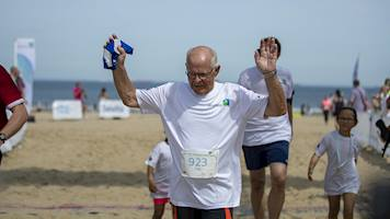 A runner raising his hands in celebration after completing the 5k event at the Aramco Beach Run.