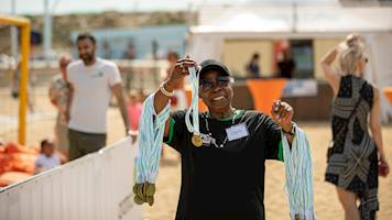 A local volunteer posing with Aramco Beach Run medals, that she is handing out to all those who completed the run.